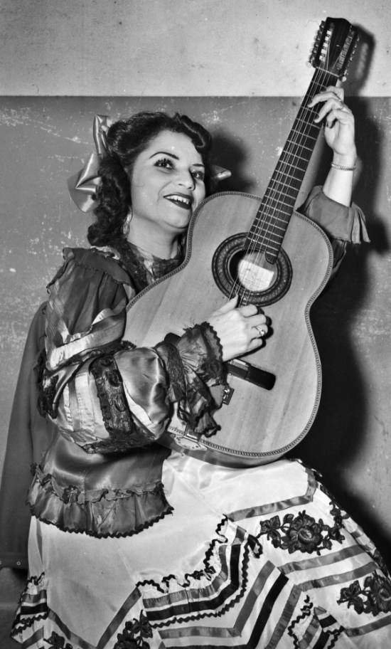 "Lydia Mendoza, ""The Lark of the Border,"" poses with her guitar at the time she was appearing at the Nacional Theater in San Antonio, January 1948.  (MS 359:  L-3514-A).   Mendoza (1916-2007), the first star of recorded Tejano and Norteno music, began singing as a child with her family on the plazas of San Antonio.   She achieved national prominence and was awarded the National Medal of Arts and numerous other awards."