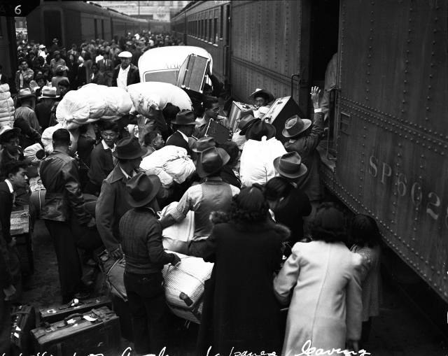 """Evacuees"" in Los Angeles load their baggage onto a train that will take them to an ""assembly center."" Clem Albers, 1942"